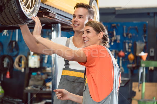 Two dedicated auto mechanics smiling while checking the wheels of a tuned car Stock photo © Kzenon
