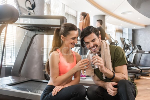 Cheerful young man and woman drinking plain water during break at the fitness Stock photo © Kzenon