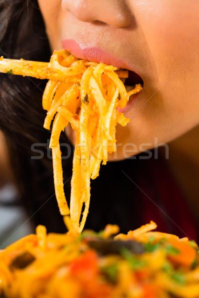 Asian woman eating pasta with chopsticks Stock photo © Kzenon