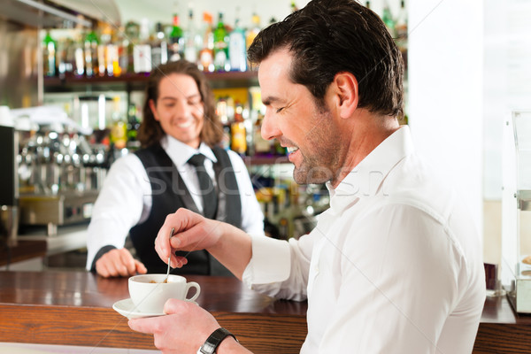 Barista with client in his cafe or coffeeshop Stock photo © Kzenon