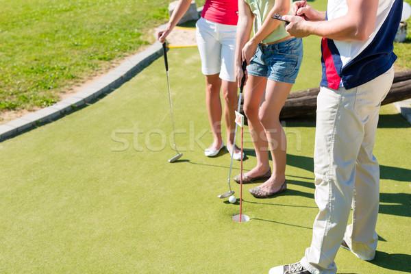 Emberek játszik miniatűr golf kint férfi Stock fotó © Kzenon