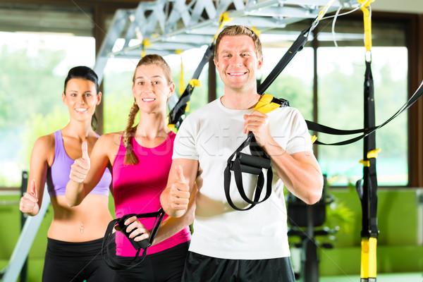 People in sport gym on suspension trainer Stock photo © Kzenon