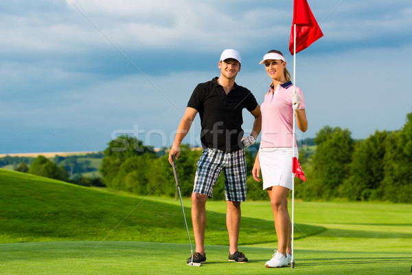 Young sportive couple playing golf on a course Stock photo © Kzenon