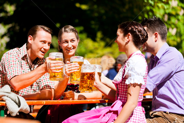 Two happy couples sitting in Beer garden Stock photo © Kzenon