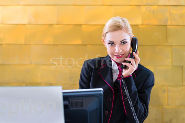 Hotel receptionist with phone on front desk Stock photo © Kzenon
