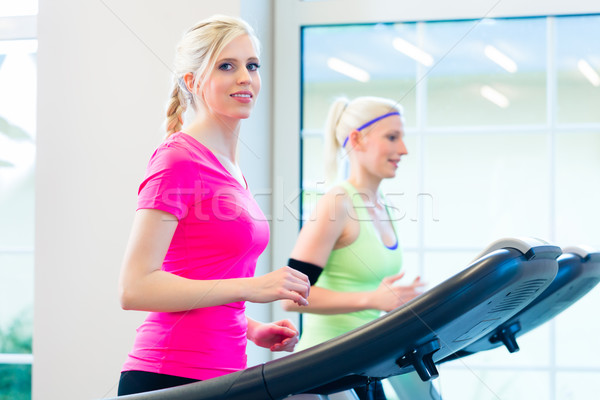 Women in gym doing sport on treadmill Stock photo © Kzenon