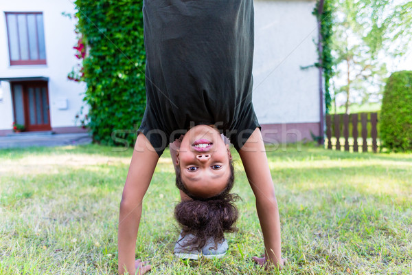African girl playing on meadow in front of home Stock photo © Kzenon