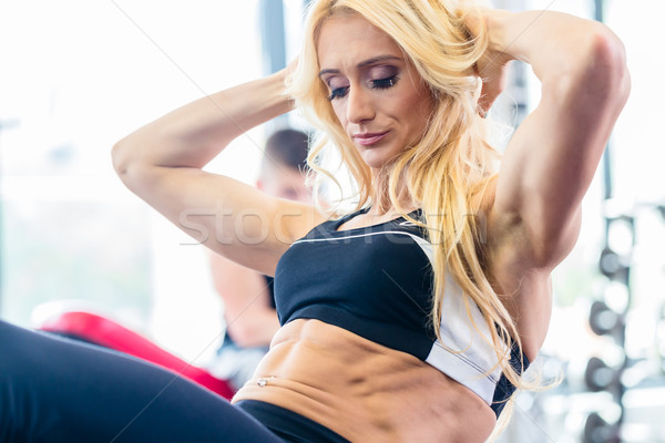 Bodybuilding woman doing sit-up in fitness gym Stock photo © Kzenon