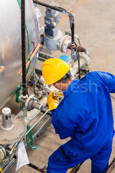 Industrial worker working at machine Stock photo © Kzenon