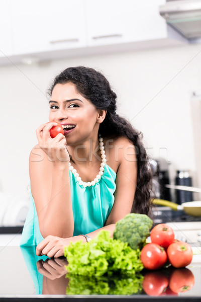 Stock photo: Indian woman eating healthy apple in her kitchen
