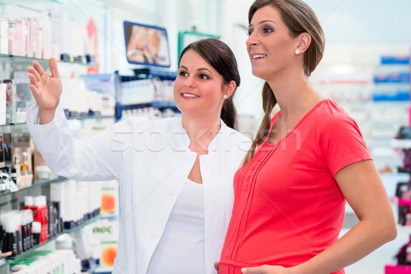 Pharmacist showing pregnant woman drugs in pharmacy Stock photo © Kzenon