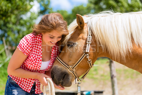 Woman feeding horse on pony farm Stock photo © Kzenon