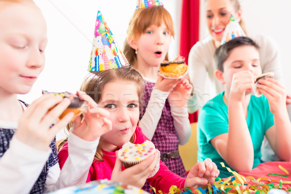 Children at birthday party with muffins and cake Stock photo © Kzenon