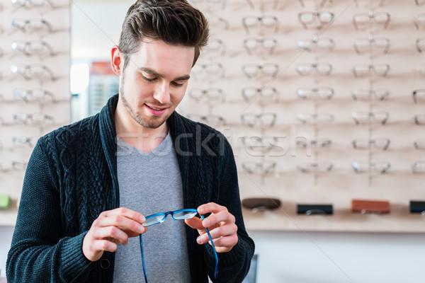 Man in front of shelf with glasses in optician shop Stock photo © Kzenon