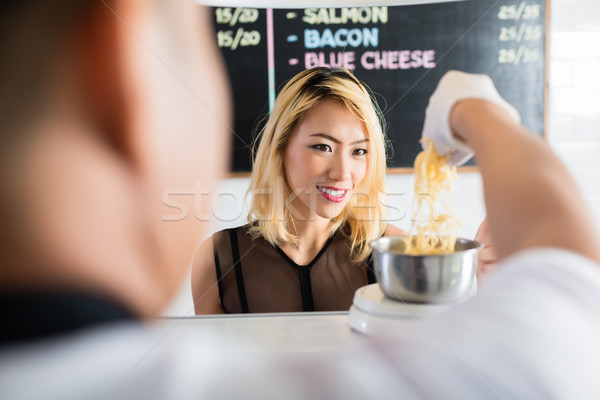 Asian woman watching as cheese is put on a scale Stock photo © Kzenon