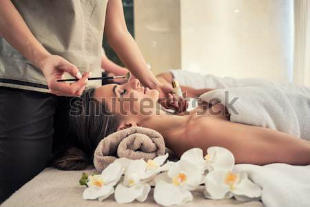 Woman relaxing under the therapeutic effect of a crystal placed  Stock photo © Kzenon