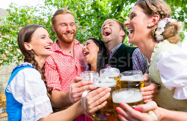 Friends having fun in beer garden while clinking glasses Stock photo © Kzenon