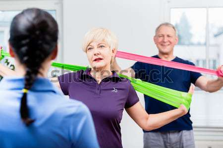 Older patients in physiotherapy using power band for strength tr Stock photo © Kzenon