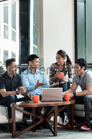 Team of four dedicated employees working together Stock photo © Kzenon