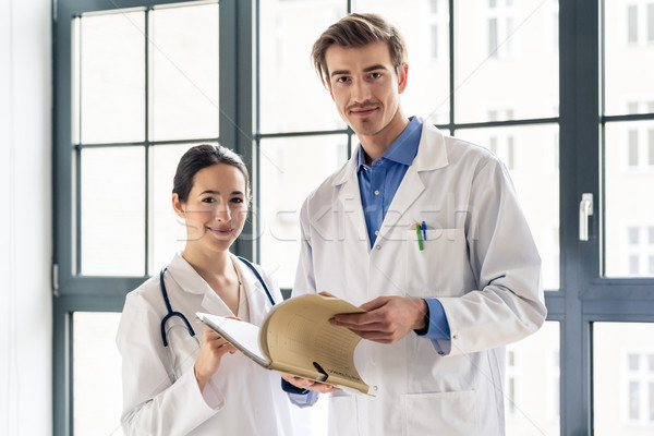 Two dedicated doctors smiling at camera Stock photo © Kzenon