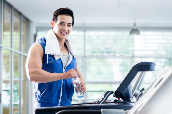 Smiling young man on treadmill holding water bottle Stock photo © Kzenon