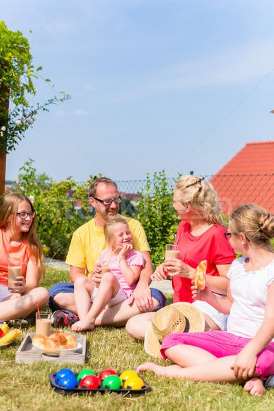 Family having picnic in garden front of their home Stock photo © Kzenon