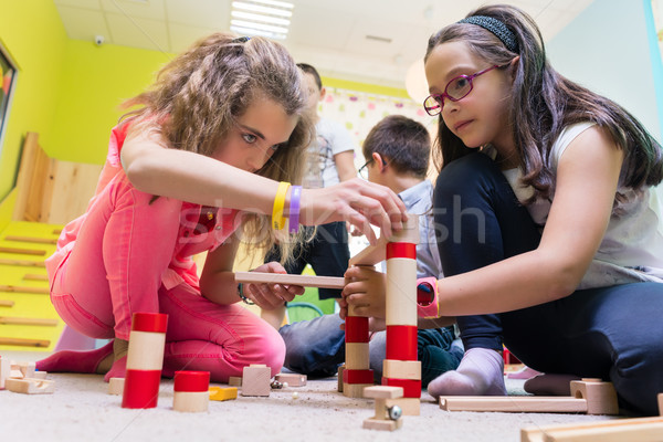 Two girls playing together with wooden toy blocks on the floor at kindergarten Stock photo © Kzenon