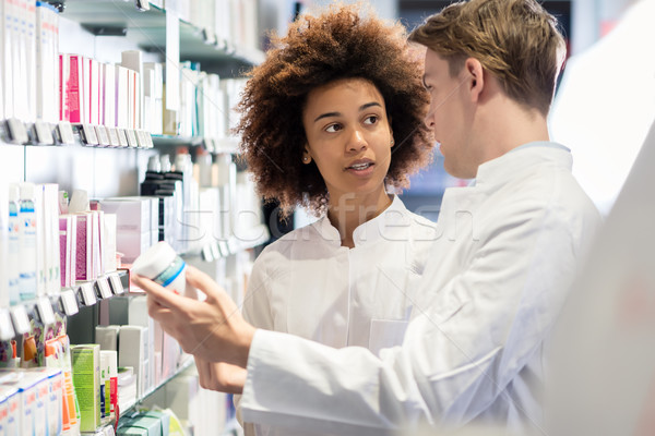 Dedicated pharmacist talking with colleague about attributes of new medicine  Stock photo © Kzenon