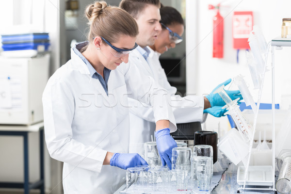 Female lab technician with safety goggles Stock photo © Kzenon