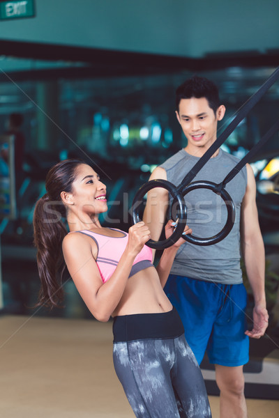 Fit woman doing ring biceps curl exercise during training Stock photo © Kzenon