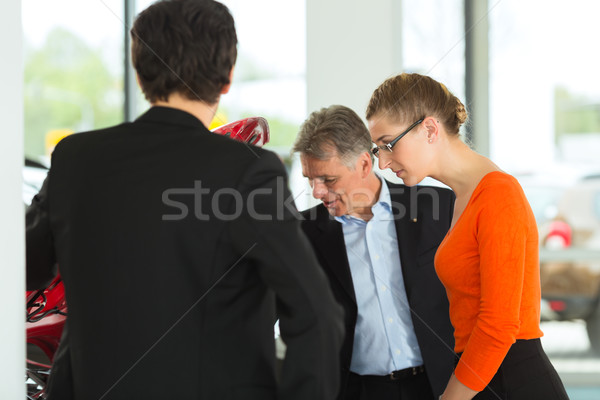 Mature man with young couple and auto in car dealership are looking beneath a hood Stock photo © Kzenon