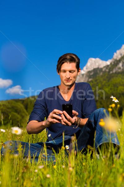 man with phone  sitting in the mountains  Stock photo © Kzenon