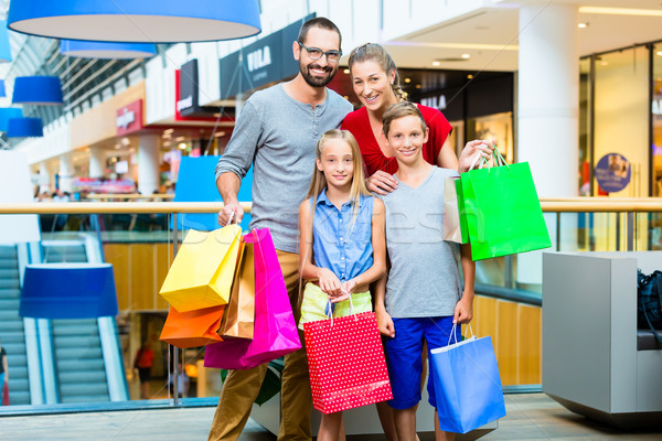 Family of four in shopping mall with bags Stock photo © Kzenon