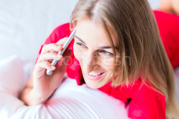 Woman telephoning on bed with smartphone  Stock photo © Kzenon