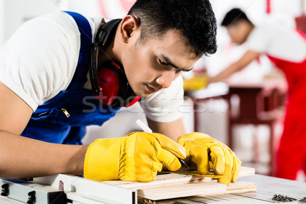 Diligent worker in factory working on wood Stock photo © Kzenon