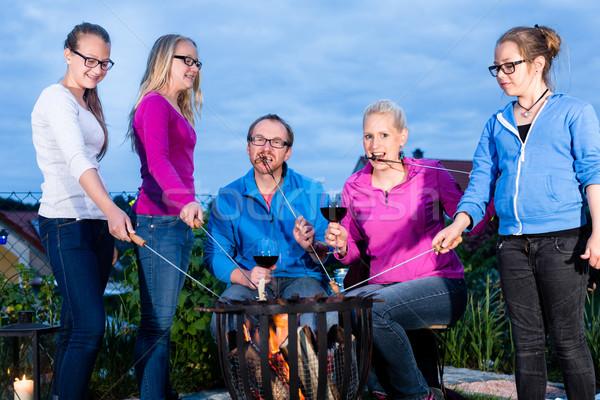Familie beim Grillen abends im Garten Stock photo © Kzenon