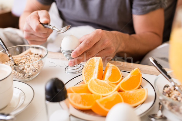 Man cracking open a boiled egg for breakfast Stock photo © Kzenon