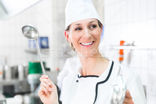 Happy female chef in restaurant kitchen waving dipper Stock photo © Kzenon