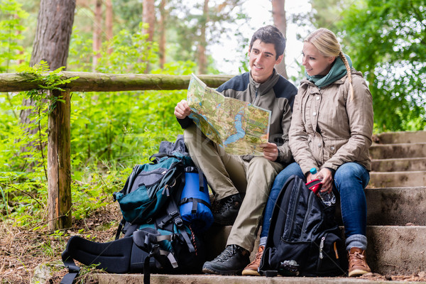 Man and woman on hike planning next route section on map Stock photo © Kzenon