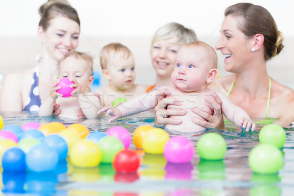 Mothers and sucklings at baby swim course playing with balls  Stock photo © Kzenon