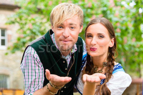 Couple in Bavarian clothes blows a kiss Stock photo © Kzenon