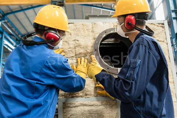 Workers applying insulation material to an industrial boiler Stock photo © Kzenon