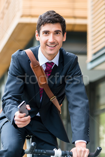 Multitasking young businessman riding a bicycle to work Stock photo © Kzenon