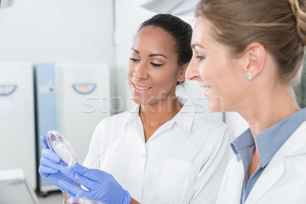 Stock photo: Scientists in research lab with analyzing instrument talking abo
