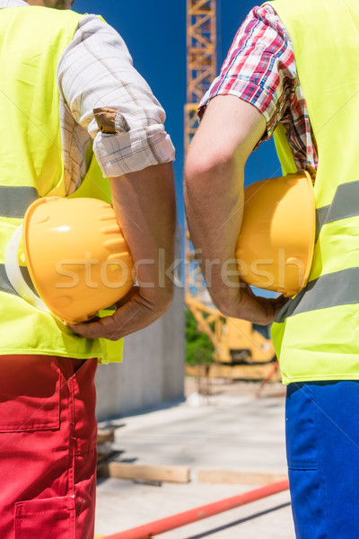 Rear view of the hands of two workers holding yellow hard hats Stock photo © Kzenon