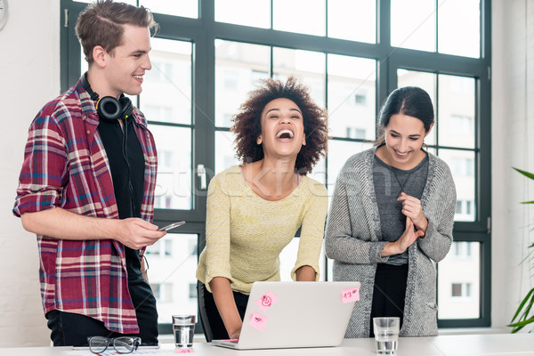 Three young colleagues laughing in the meeting room Stock photo © Kzenon