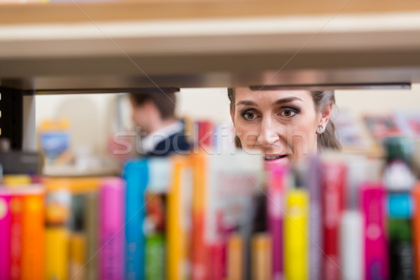 Woman looking thru shelf of books choosing volume to read Stock photo © Kzenon