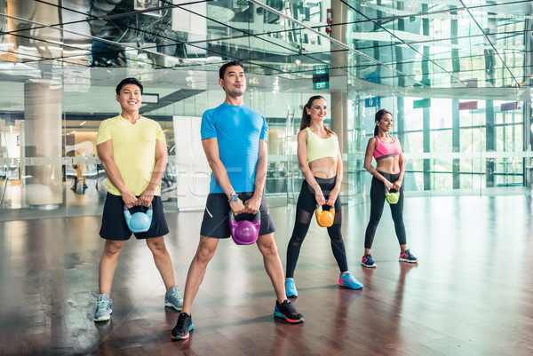 Full length view of four cheerful people holding kettlebells during training Stock photo © Kzenon