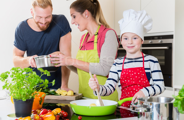 Family cooking together in kitchen Stock photo © Kzenon