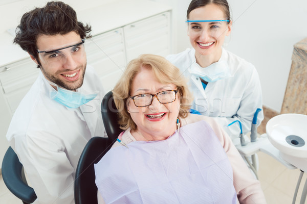 Dentists and patient in surgery looking at camera Stock photo © Kzenon